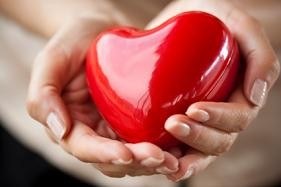 Woman holding a red heart in palms of hands