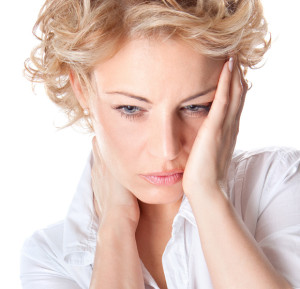 Blonde woman holding her face and neck in pain